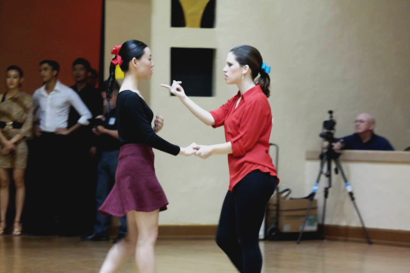 """I am wearing a red button-down, black leggings, and a ponytail with a teal bow. Yibing, a young woman with light skin, black hair in a fishtail braid, and a red bow, is wearing a black leotard and burgundy skirt. We are dancing, and I am making a """"come hither"""" gesture at her."""