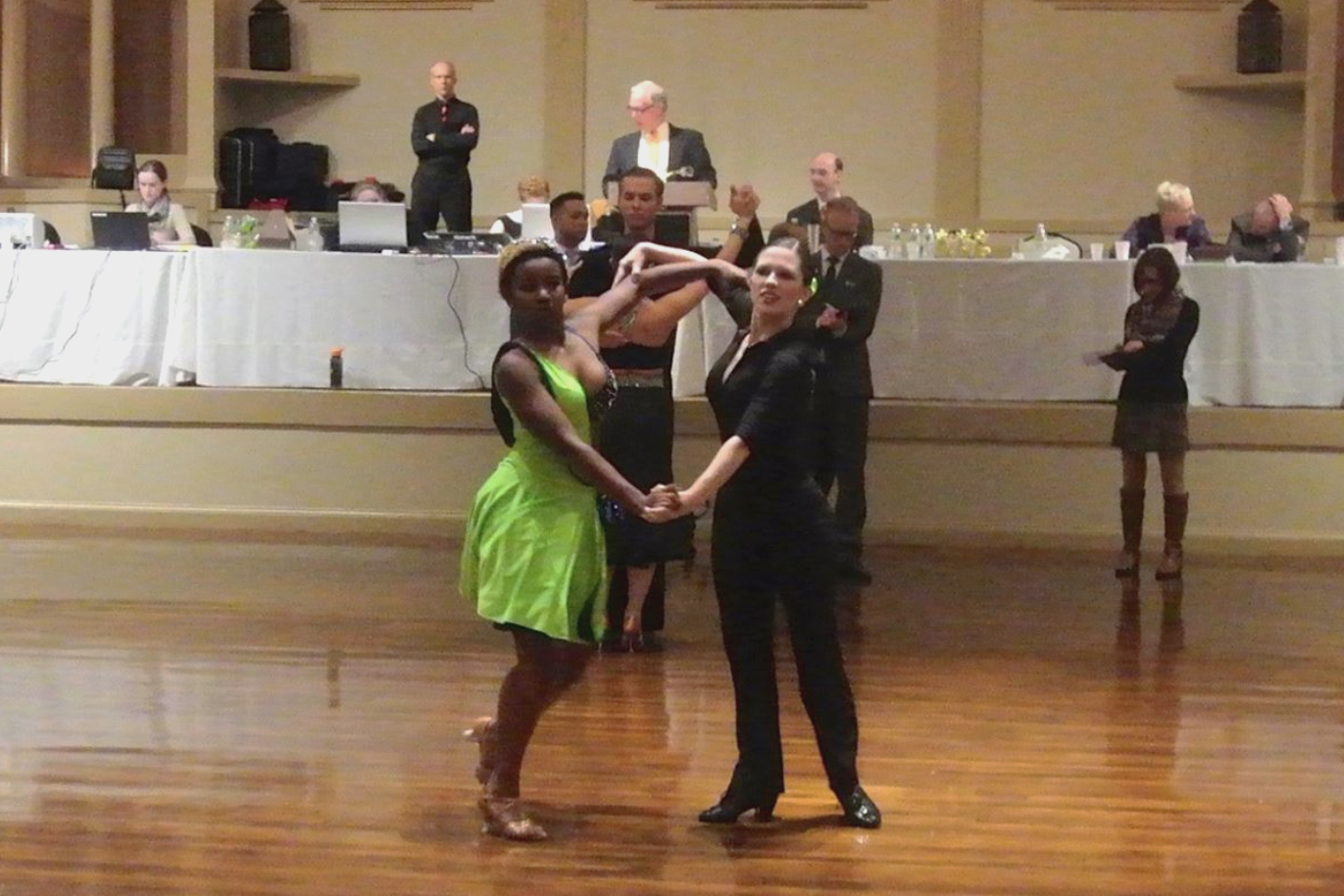 I am dancing with Danielle. I am wearing a black leotard, black pants, black practice shoes, and a green hair bow. Danielle is a green and navy blue Latin dress and Latin shoes. We are dancing the last la passe in our routine.