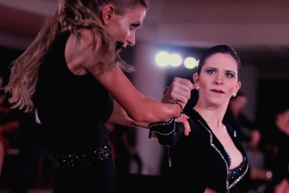 I am wearing a black stoned Latin shirt, black pants, and black Latin shoes. I am leading Katie, a woman with wavy blonde hair in a half-up, half-down hairstyle and pale-but-tanned skin. We are dancing in an open-level paso doble event at Harvard Invitational 2018.