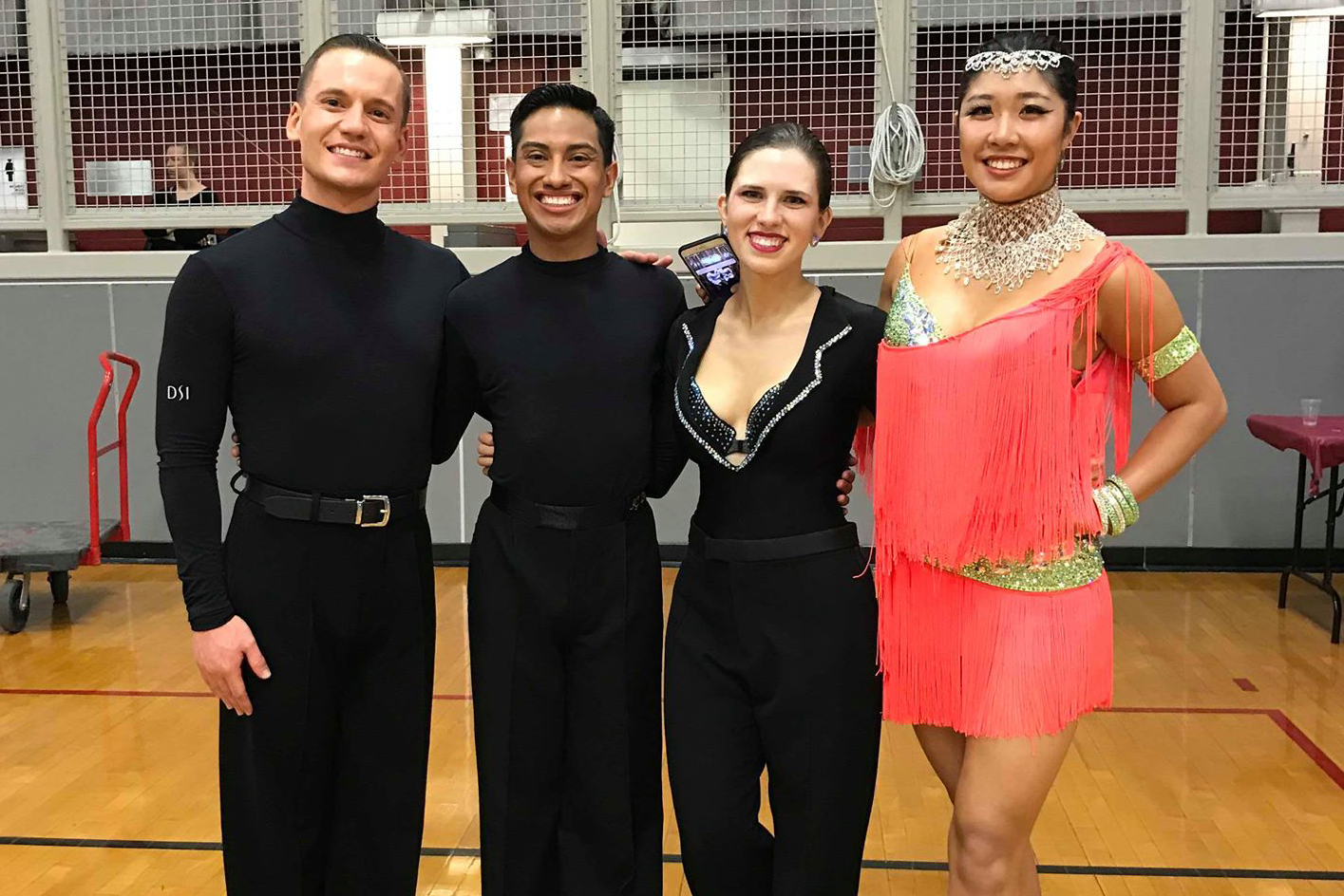 From left to right: The other same-sex couple in pre-champ Latin. Two men, both wearing black dance turtlenecks, black pants, and black shoes. Then me, in my black Latin shirt and black Latin shoes, but this time with a pair of Men's Dance Pants. On the right is my new partner Michelle, who has black and purple hair in a bun with a silver headpiece, a silver collar, and a silver, green, and salmon pink fringed dress, along with green bracelets and tan Latin shoes. We are standing in MIT's Rockwell Cage.